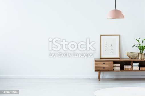 Retro pink ceiling lamp above a wooden sideboard in a modern living room interior with an empty white wall and copy space