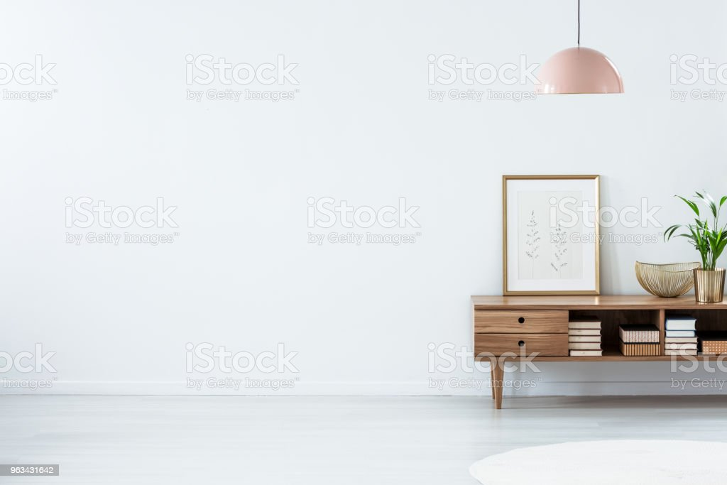 Pink lamp above wooden sideboard stock photo
