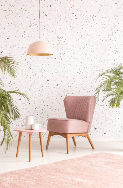 Pink lamp above wooden table and armchair in pastel living room interior with plants. Real photo Pink lamp above wooden table and armchair in pastel living room interior with plants. Real photo wallpaper decor stock pictures, royalty-free photos & images