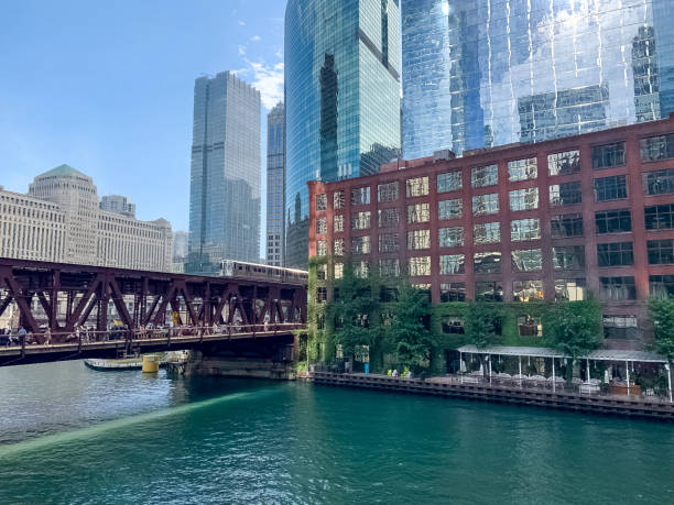 pink line el train crossing lake street over chicago river as pedestrians cross on sidewalk between river and track during summer - ivy corporate building imagens e fotografias de stock