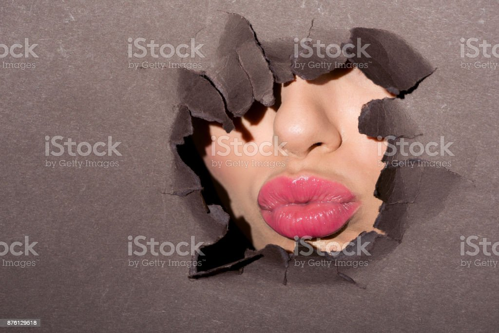 pink lips of woman peeking out of ragged hole in dark paper