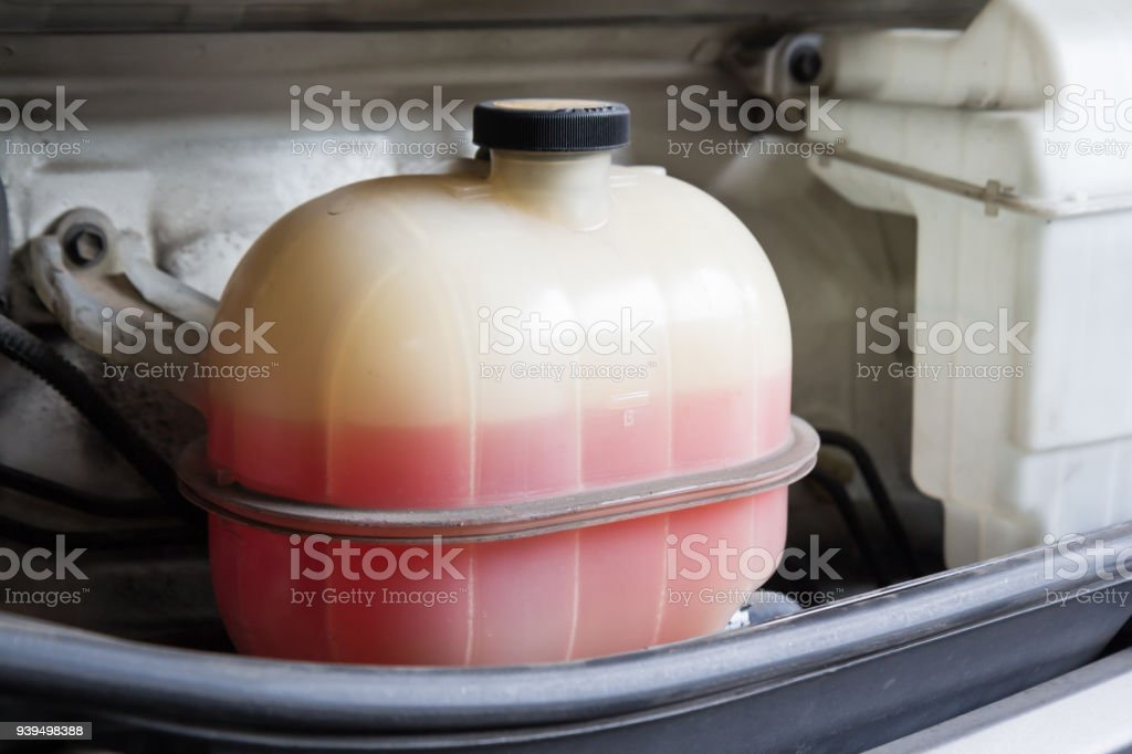 pink liquid in plastic coolant tank  for car cooling system stock photo