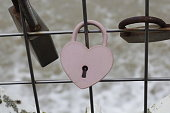Love heart shape, aged Pink padlock, attached to silver metal wire fence, in front of frothy water foam with Old gold lock surrounding it