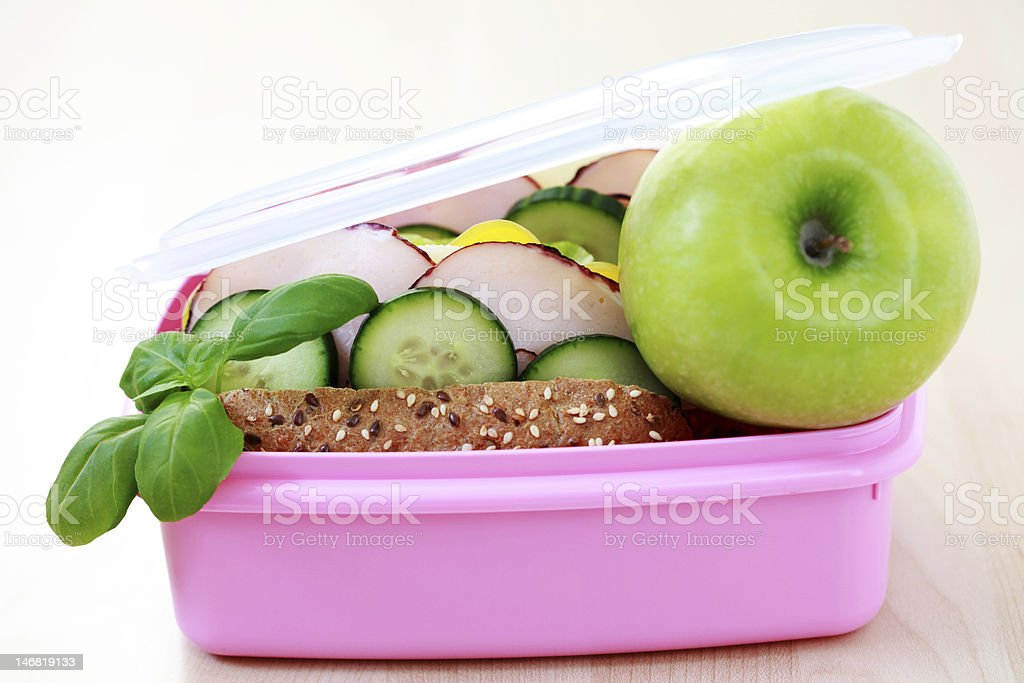 Pink lunch box with a sandwich and a green apple to eat royalty-free stock photo