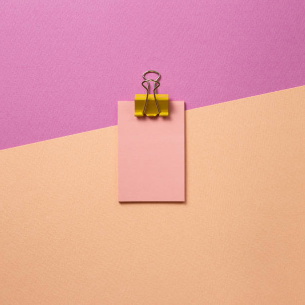 Pink memo paper, sticky notes with yellow binder clip on pink background. top view, copy space stock photo