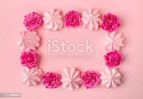 157527860 istock photo Pink meringues on a pink background with roses laid out in the form of a frame. Idea, concept as background texture, backdrop. 1127388953