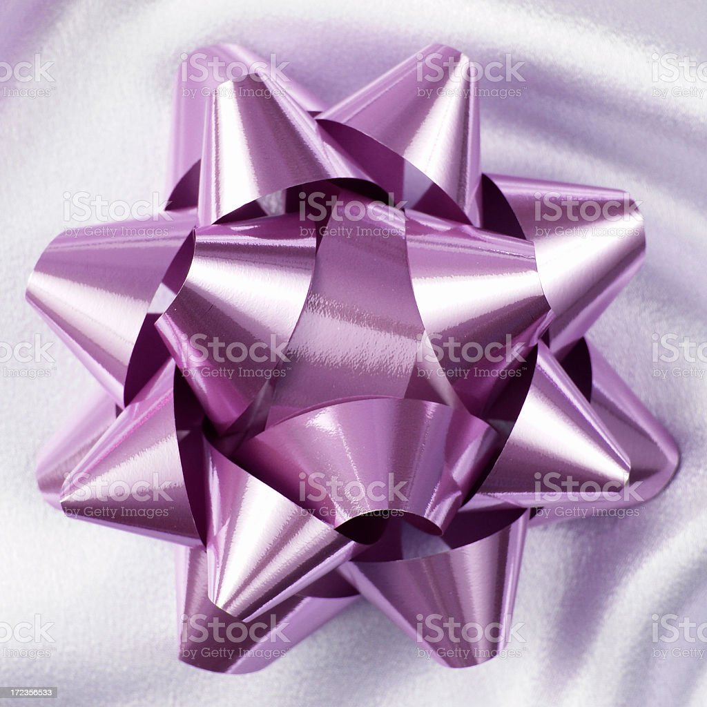 Pink metallic bow on satin fabric royalty-free stock photo