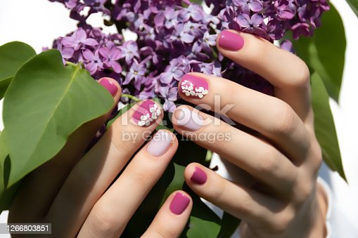 istock Pink nail design. Female hand with pink manicure holding purple lilac. 1266803851