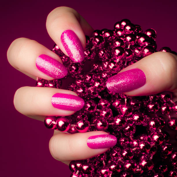 pink nails manicure Shiny glittering pink nails with pink pearl jewel on purple background. Manicure and nail care concept. pink nail polish stock pictures, royalty-free photos & images