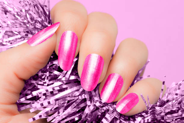 pink nails manicure Female hand with pink nails hold purple textured decoration on purple background. Manicure concept. pink nail polish stock pictures, royalty-free photos & images