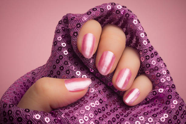 pink nails manicure Female hand with shiny bright pink lacquered nails is in purple textile material with glitters on pink background. Manicure and nail care concept. pink nail polish stock pictures, royalty-free photos & images