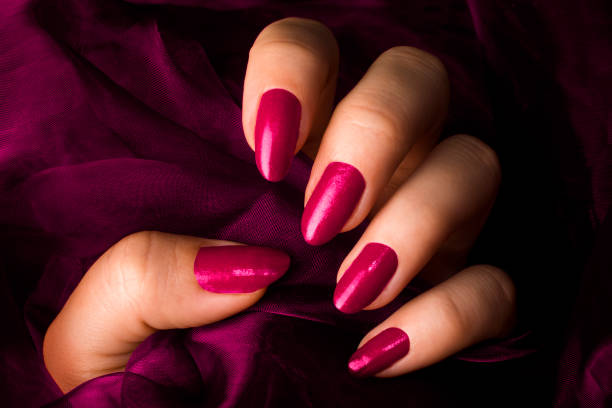 pink nails Female hand with pink nails is holding pink fabric. pink nail polish stock pictures, royalty-free photos & images