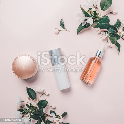 istock Pink natural cosmetics: oil, serum, cream, mask on background with flowers. Flat lay, minimalism. 1139787320