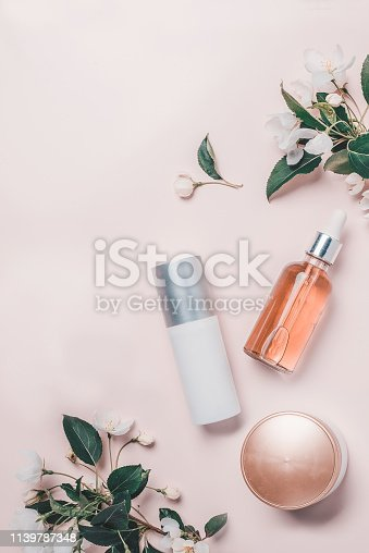 istock Pink natural cosmetics: oil, serum, cream, mask on background with flowers. Flat lay, Spa concept 1139787348