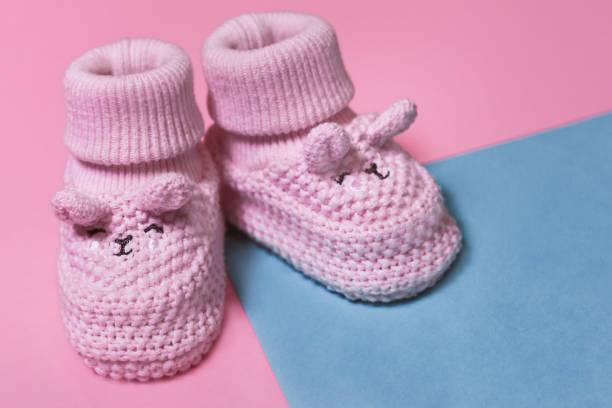 rosa neugeborenehäkeln booties auf einem pastell papier hintergrund - babyschuhe nähen stock-fotos und bilder