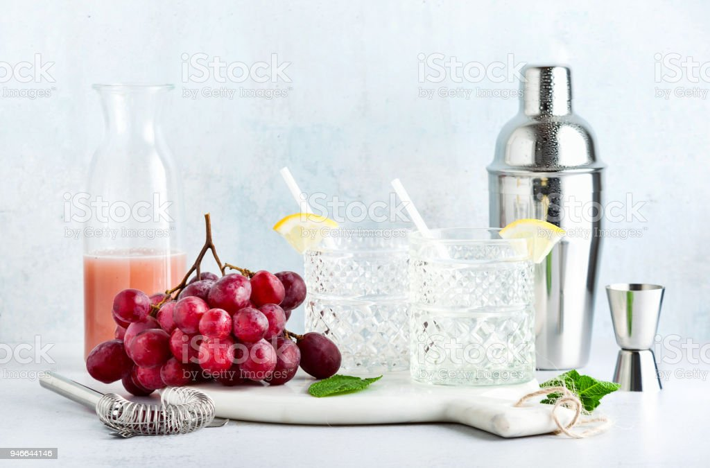 pink non-alcoholic  moсktail made from grapes with lemon and mint and shaker . summer refreshing drink stock photo