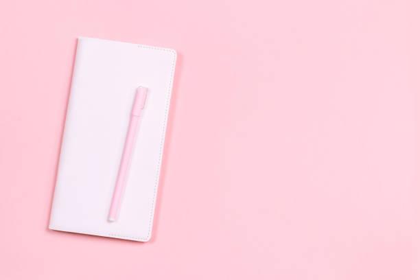 rosa notizbuch und stift notizen auf rosa pastell schreibtisch. - pastellstifte stock-fotos und bilder