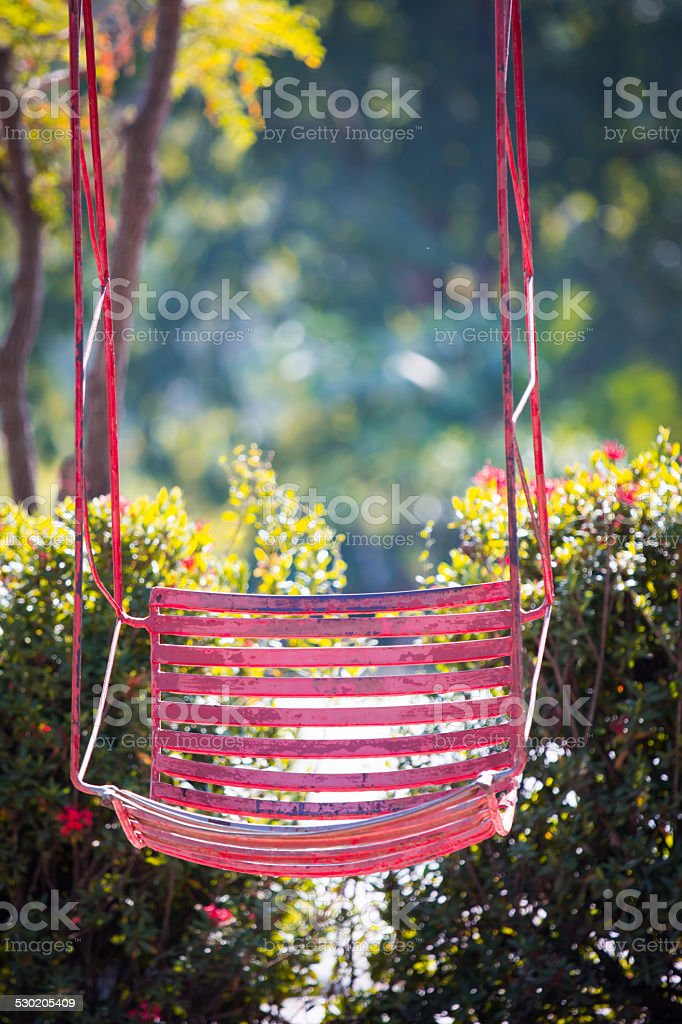 Pink old  and rusty iron swings stock photo