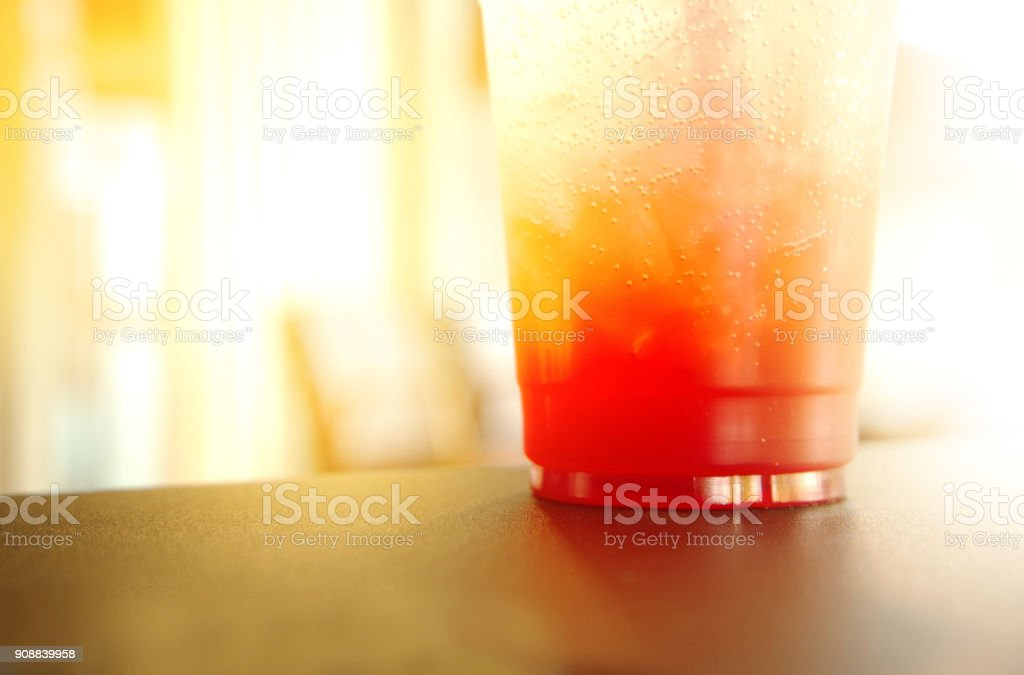 pink orange fresh drink in plastic take a way glass in the table bar or cafe background stock photo