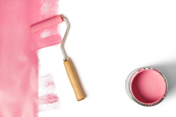 Pink paint roller on white stock photo