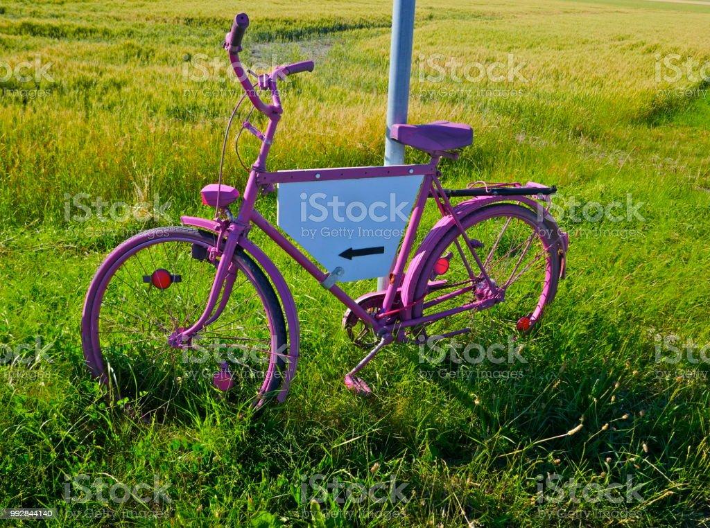 Bicicleta pintada-de-rosa com um branco, exceto por uma seta preta, o espaço publicitário sem rótulo - foto de acervo