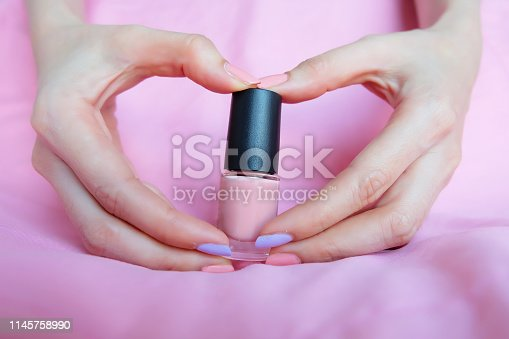 istock Pink Painted Nails. Beautiful Pink Nail Manicure with Pink Bottle in Woman is Hand on Pink Background Great for Any Use. 1145758990