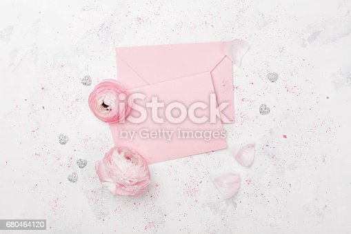 680461500istockphoto Pink paper blank and beautiful ranunculus flowers. Wedding mockup or greeting card on mother day in flat lay style. 680464120