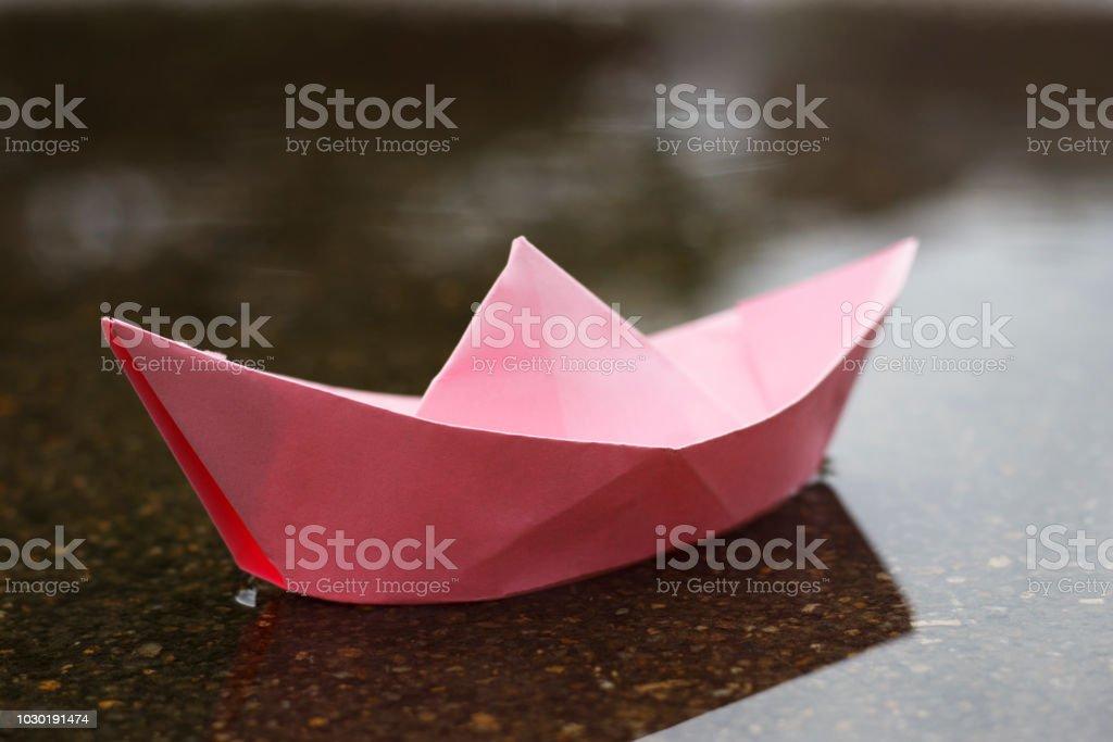 pink paper boat on wet asphalt, mood concept