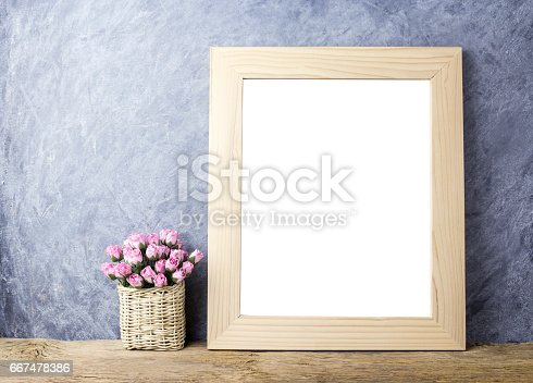 istock Pink paper rose flowers in basket and blank picture frame on old wood 667478386