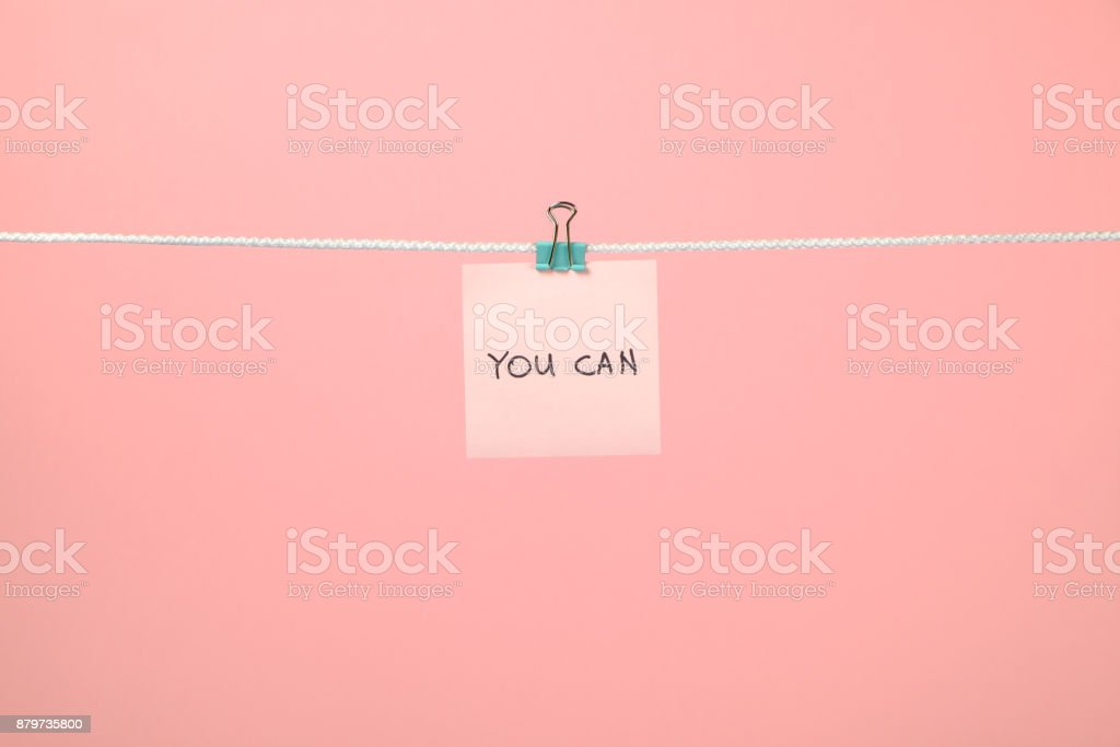 Pink paper sheet on the string with text You Can over colorful background stock photo