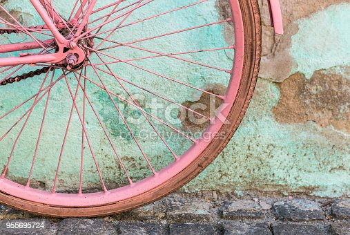 Color image depicting a pedal bicycle painted a vibrant shade of pink. The bike is leaning against an aqua blue wall that is weathered and ruined - the paint is peeling off. The bright color of the bike contrasts nicely with the hue of the wall. The bicycle is decorated with a couple of flowers. Lots of room for copy space.