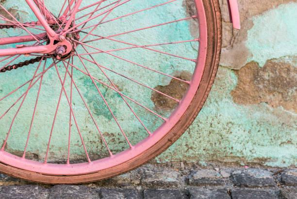 Rose vélo pédale appuyé contre le mur bleu détruit superficiel par les agents - Photo