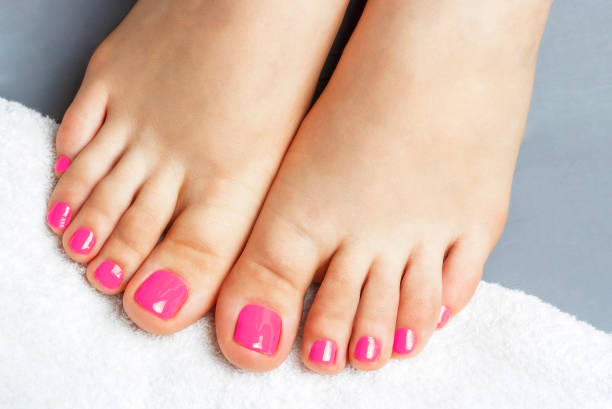 Pink pedicure close-up, isolated on a gray background, top view stock photo