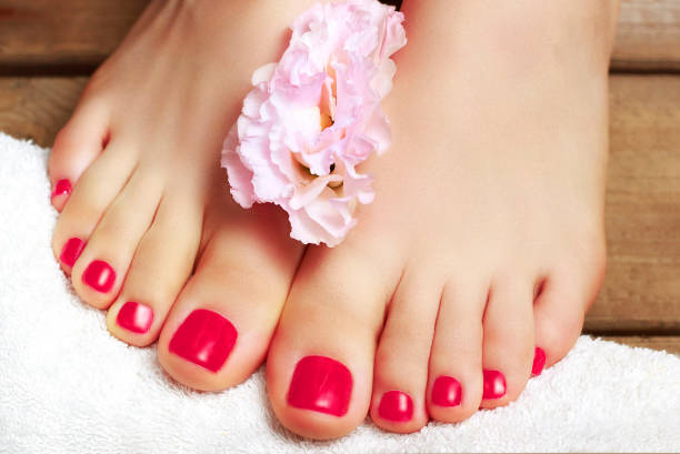 Pink pedicure with flower close-up, isolated on a wooden background, top view stock photo