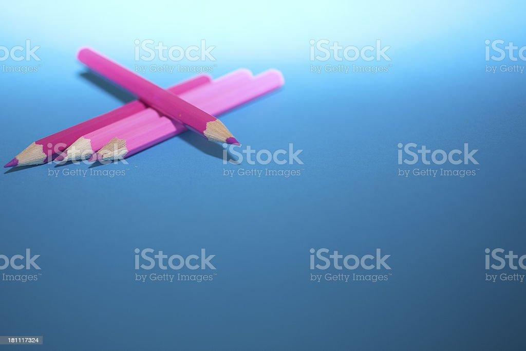 Pink pencil crayons on a blue foreground stock photo