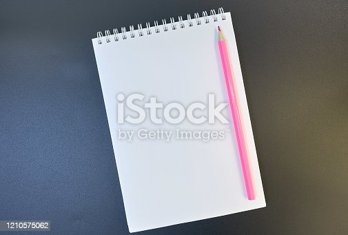 Pink pencil on a white sheet of notepad paper on a dark gradient from brown to blue background. Blank paper sheet and pencil for mock up. copy space. flat lay
