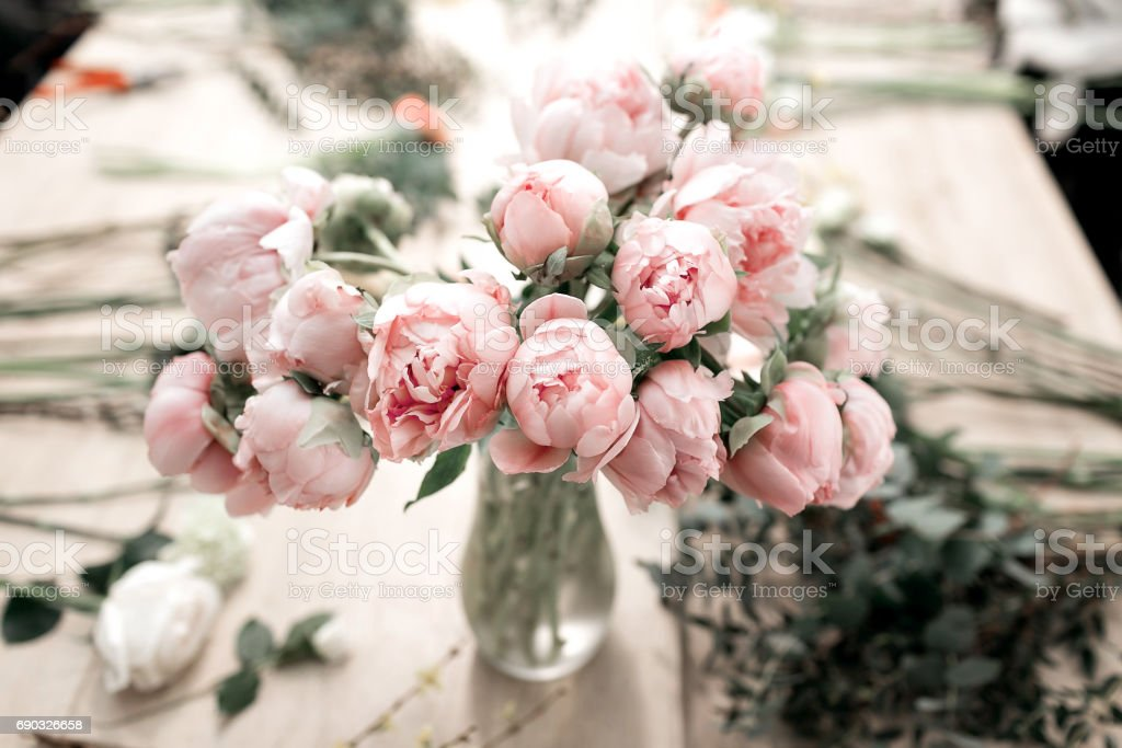 Pink peonies in vase on wooden floor and bokeh background - retro styled photo. soft focus. stock photo