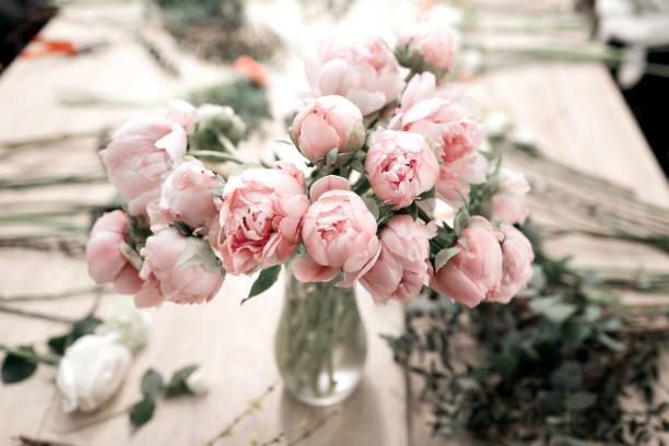 Pivoines roses dans un vase sur plancher en bois et fond de bokeh - rétro style de photo. flou artistique. - Photo
