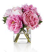 A pink peony bouquet in a square glass vase. Shot against a bright white background. There is a path which may be used to delete the reflection if desired. Extremely high quality faux flowers.