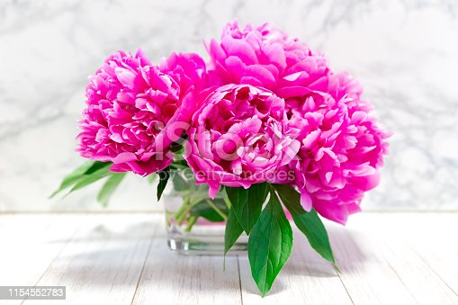 Pink peony bunch on wooden table