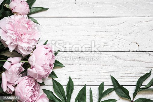 pink peony flowers over white wooden table with copy space. wedding invitation. vintage toning