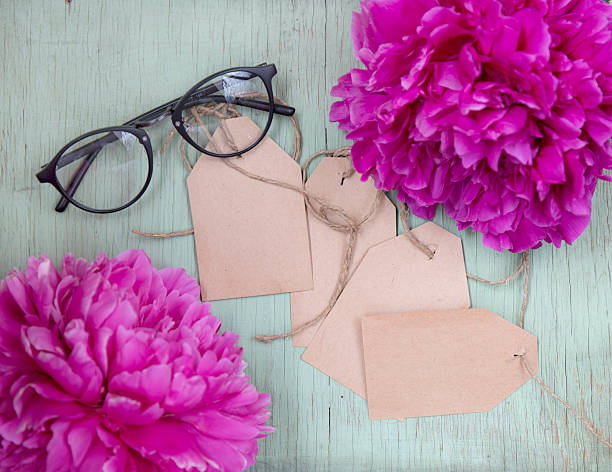 Pink peony, rough paper tag and glasses on wooden background – zdjęcie