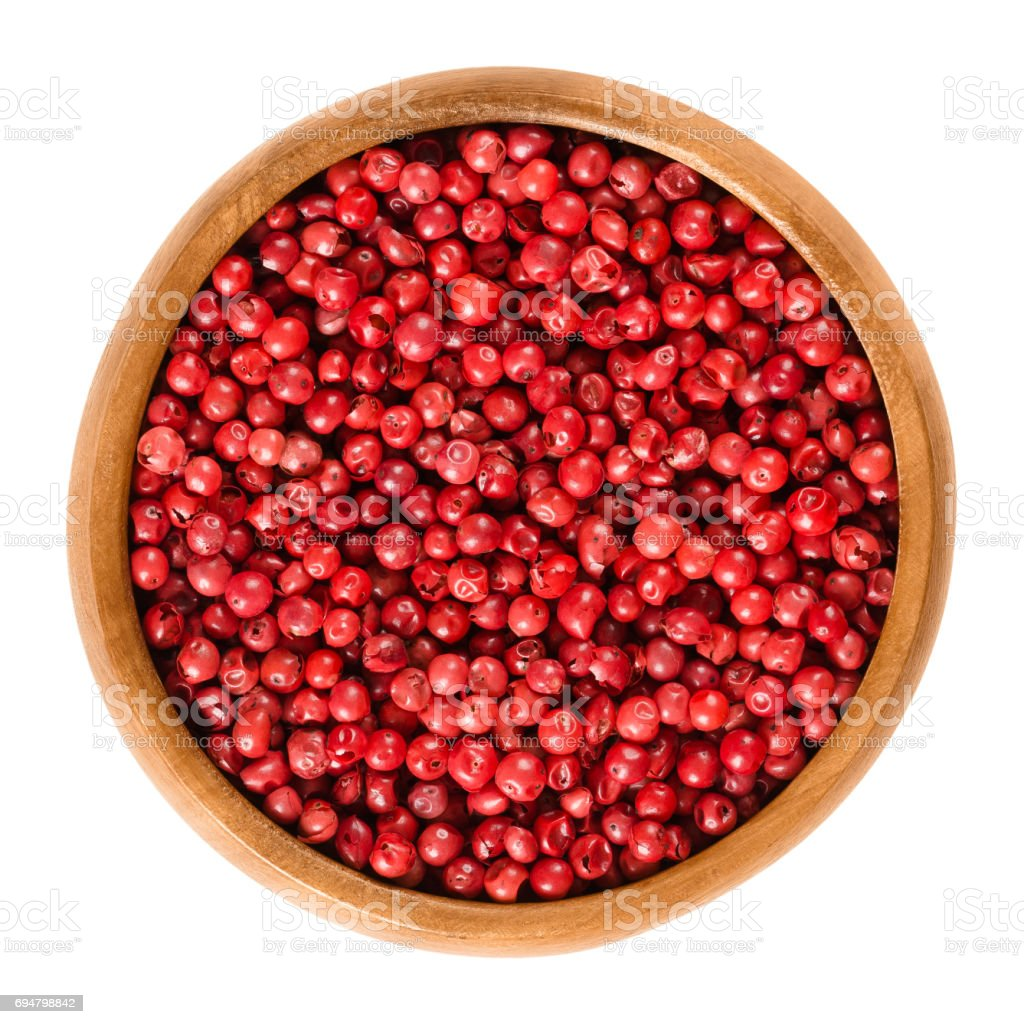 Pink pepper in wooden bowl over white stock photo