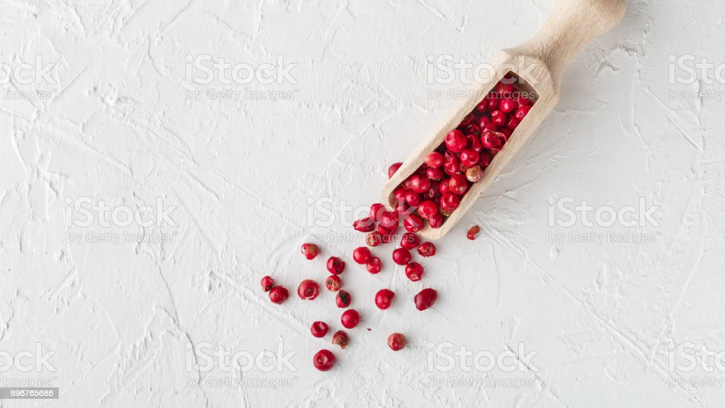 Pink pepper scattered on white textured background stock photo