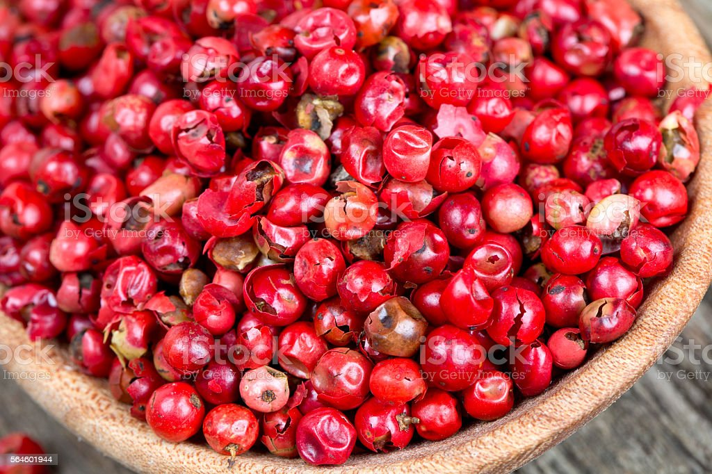 pink peppercorn in a spoon on wooden background stock photo