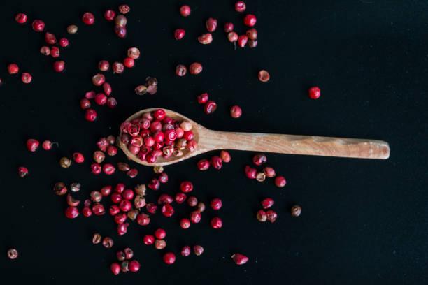 Poivre rose - épice célèbre de Brésil - sur fond noir. Vue de dessus. - Photo