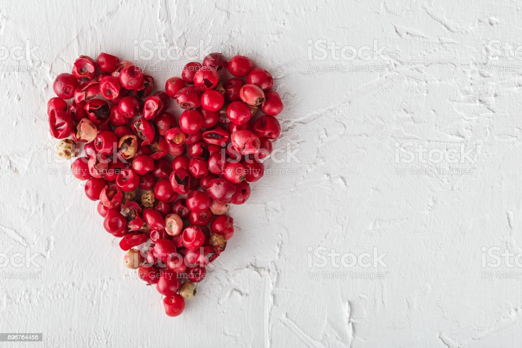 Pink peppercorns in a heart shape on white background stock photo