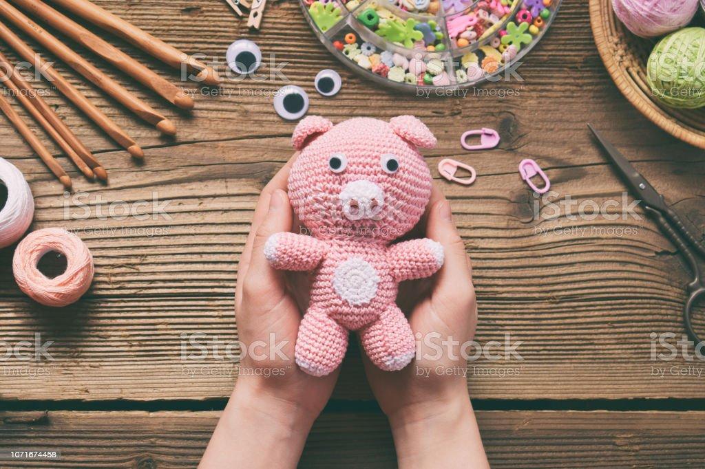 Cerdo rosa. Crochet juguetes para el niño. En la tabla hilos, agujas, gancho, hilo de algodón. Artesanías hechas a mano. Concepto de DIY. Pequeñas empresas. Ingresos de pasatiempo - foto de stock