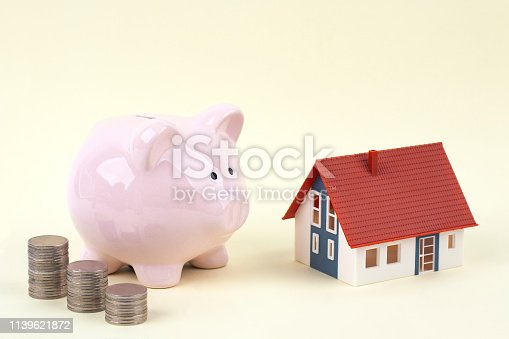 istock pink piggy bank and coins with model house 1139621872