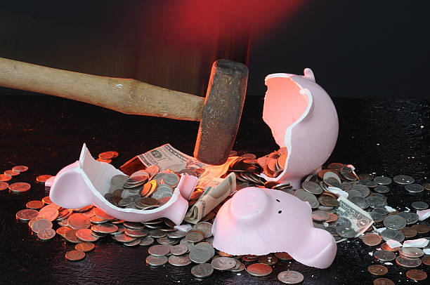 Pink piggy bank being broken by a hammer with coins stock photo